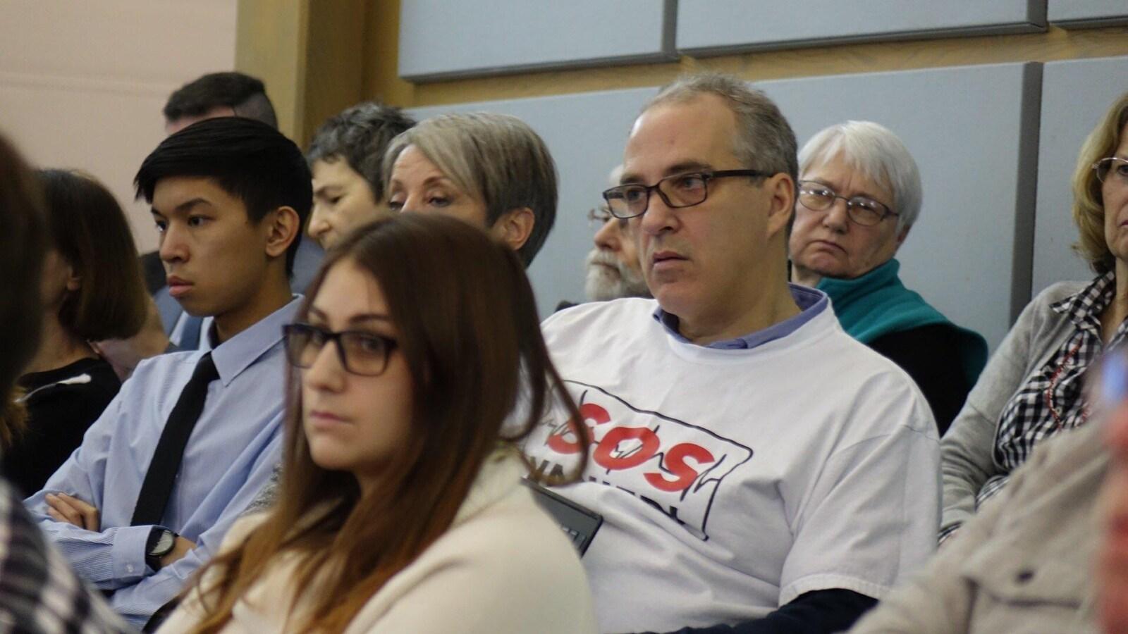L'homme est assis dans une salle, entouré d'autres personnes et écoute.