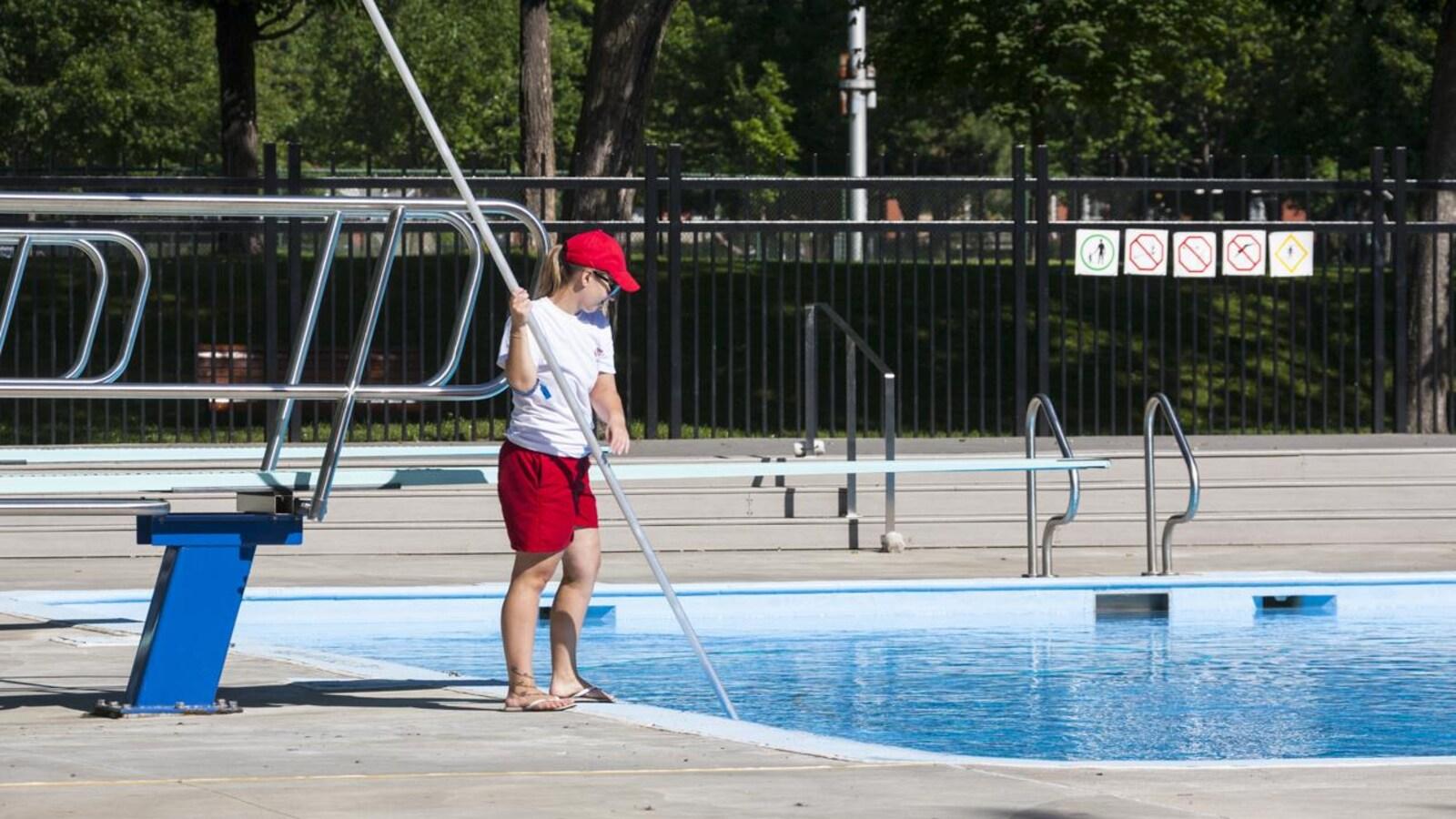 Un sauveteur nettoie la piscine Laurier, à Montréal