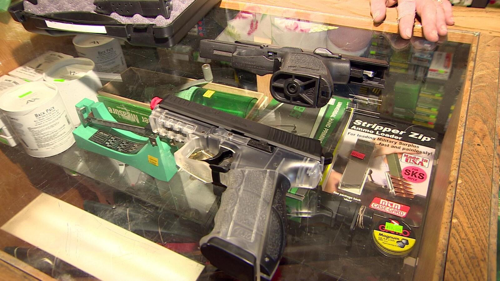 Deux pistolets l'un à côté de l'autres sont entreposés sur le comptoir d'un magasin d'armes à feu.