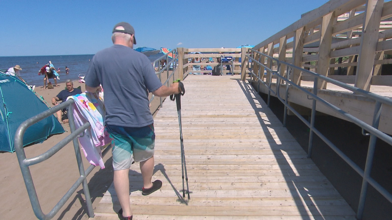 Un homme marche sur une passerelle à la plage à l'aide d'une canne.