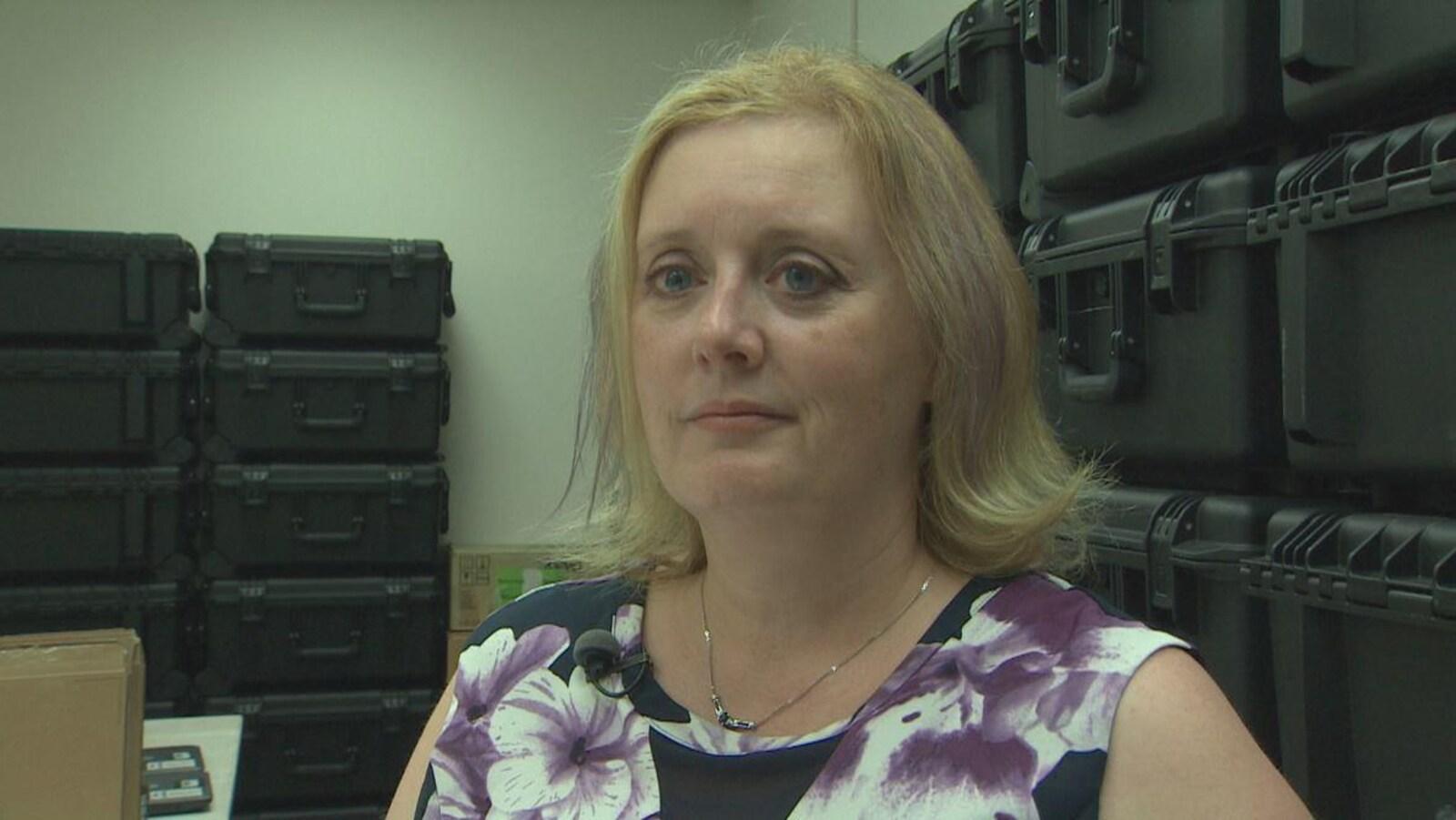 Kim Poffenroth en entrevue entourée de boîtes de scrutin