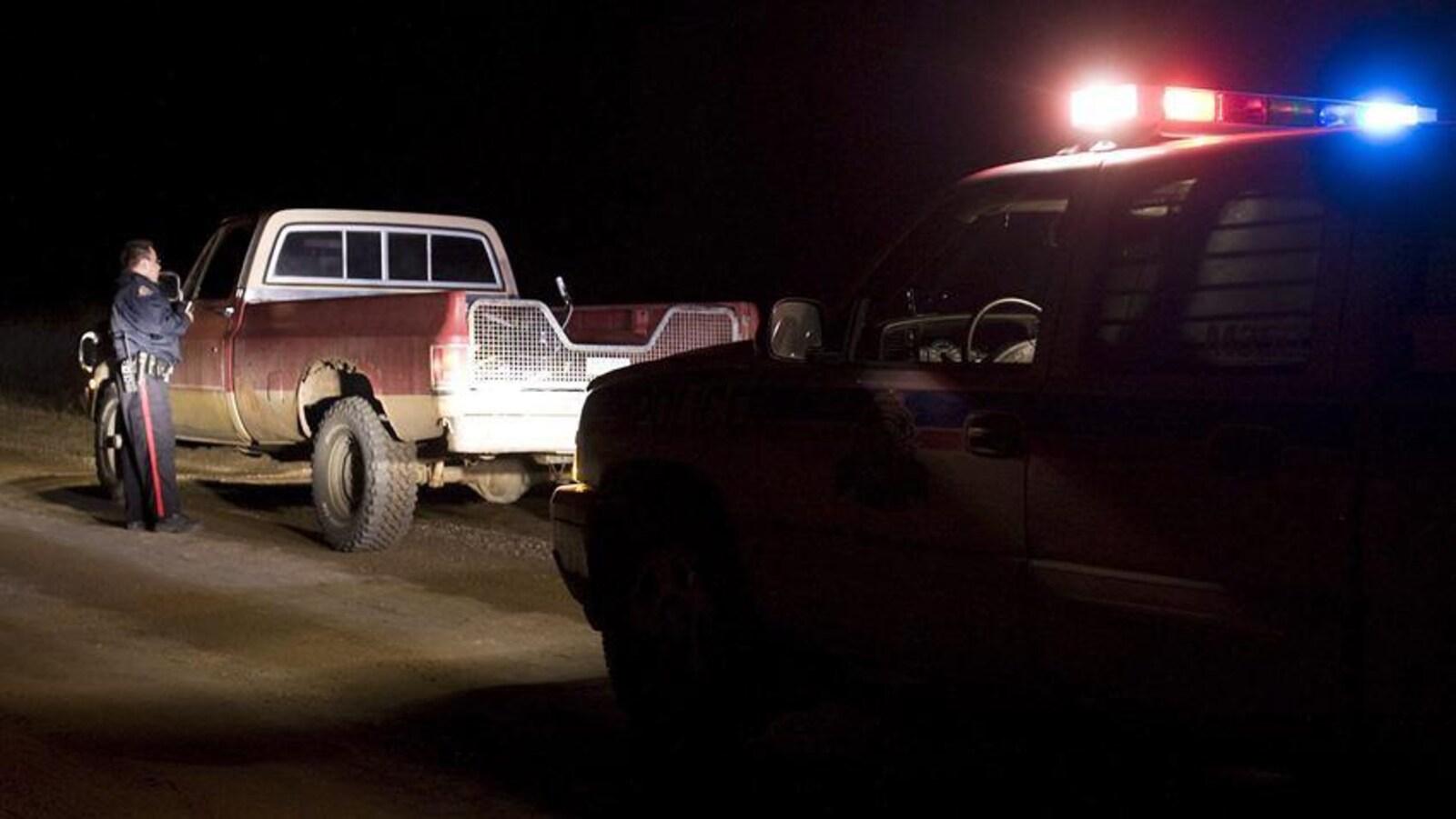 Un contrôle de véhicule de nuit, sur une route en terre. Un véhicule de police au gyrophares allumés éclaire une camionnette à plateau arrêtée sur le bas côté. Un policier debout à côté de ce véhicule semble parler au conducteur.