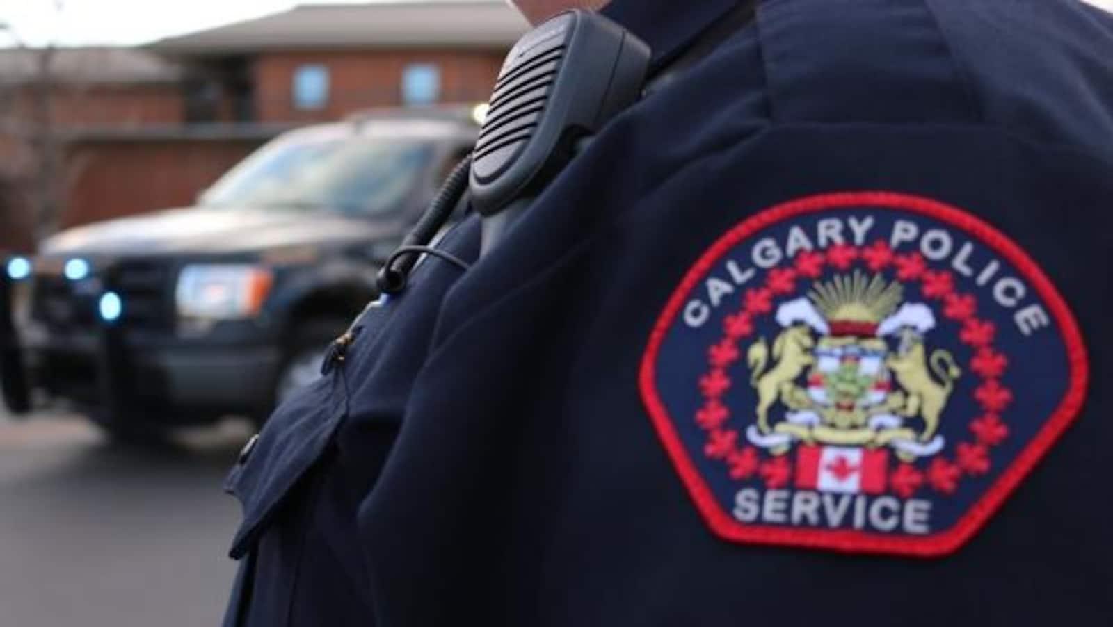 """Photo en gros plan de la poitrine d'un policier de Calgary. Son écusson en avant- plan dit """"Calgary police service""""."""