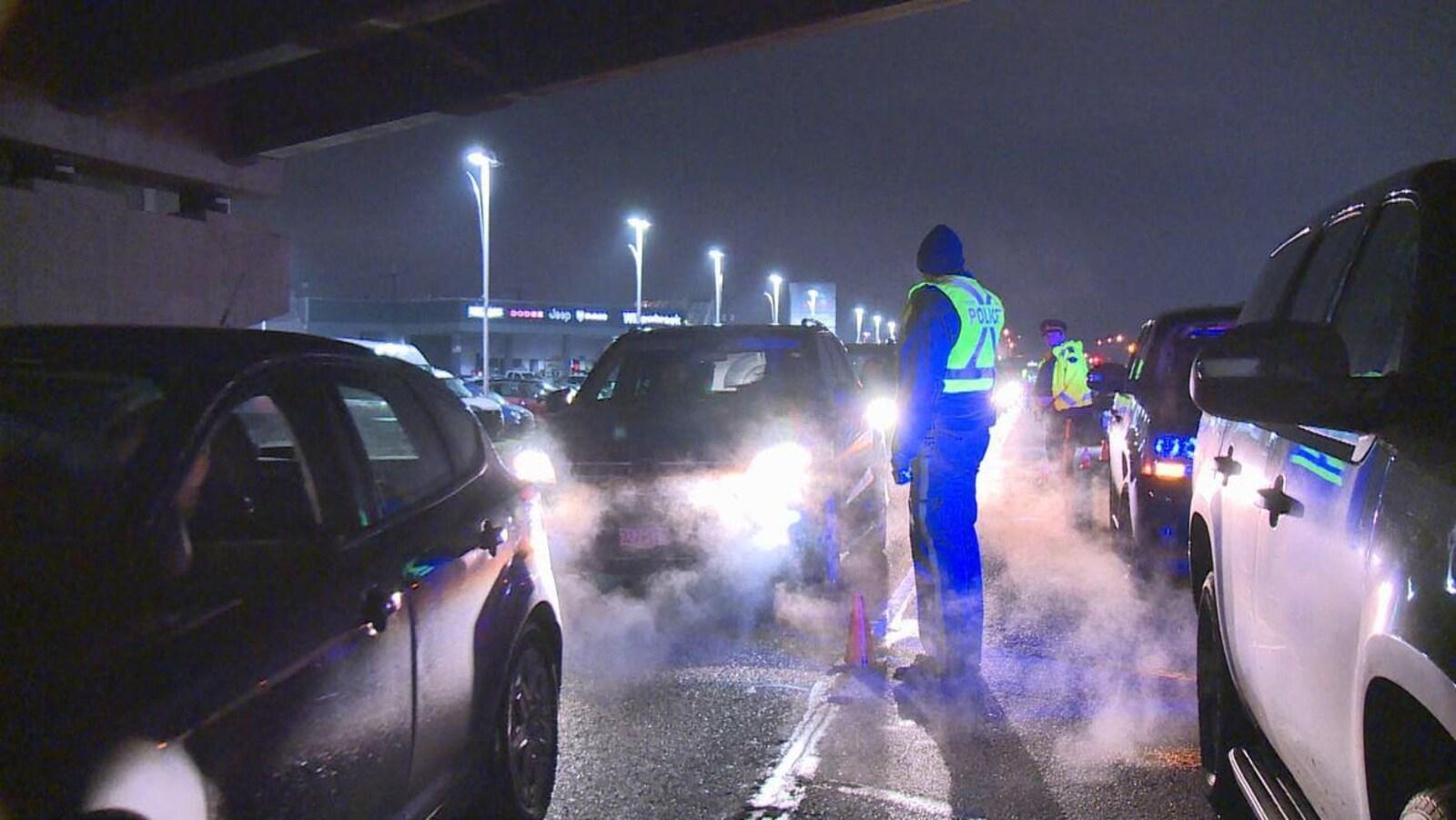 Deux policers, le soir, entre deux files de voiture.