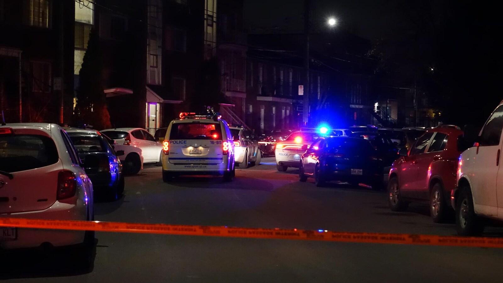 Cordon et véhicules de police devant des résidences.