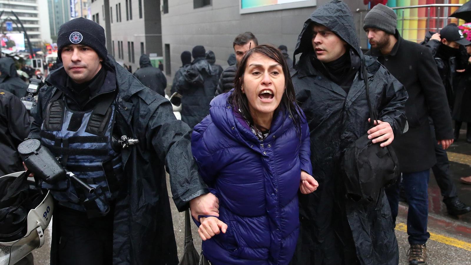 Une femme vêtue d'un imperméable violet est tenue au bras droit par un policier turc.