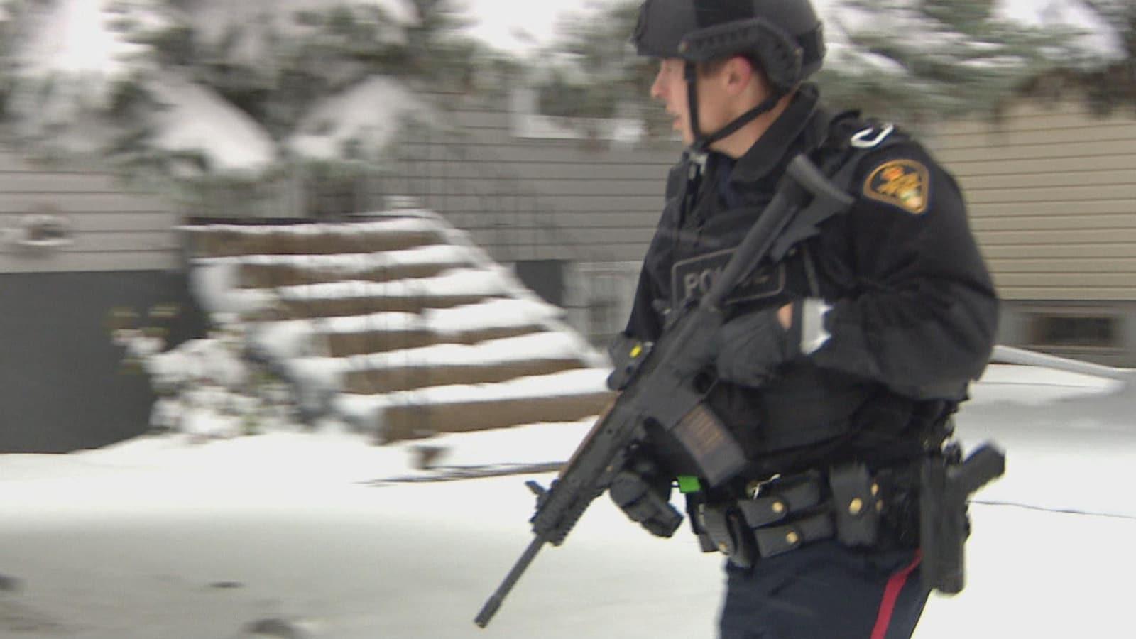 Un policier porte une arme dans ses mains.