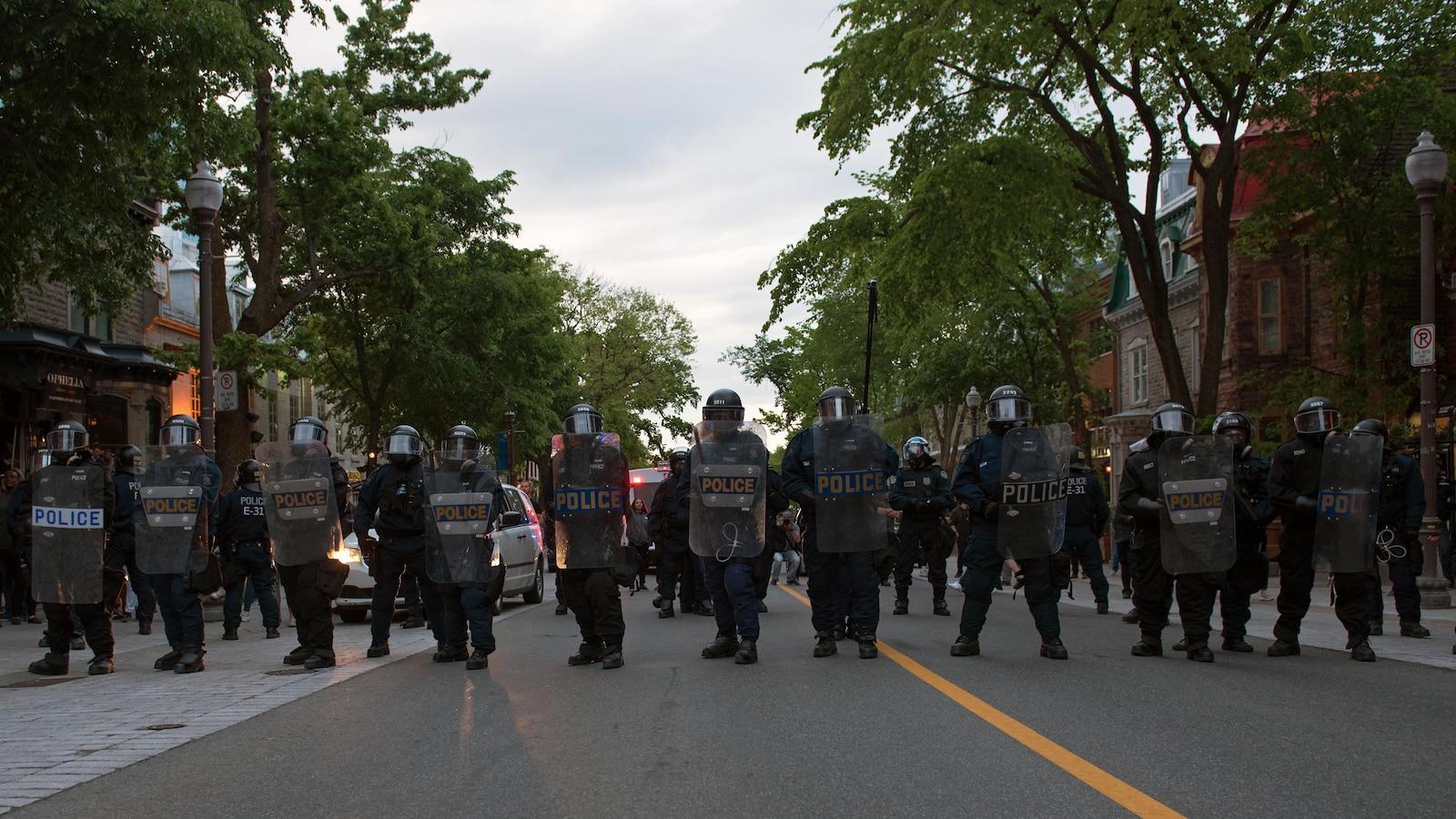 Une rangée de policiers casqués levant leurs boucliers.