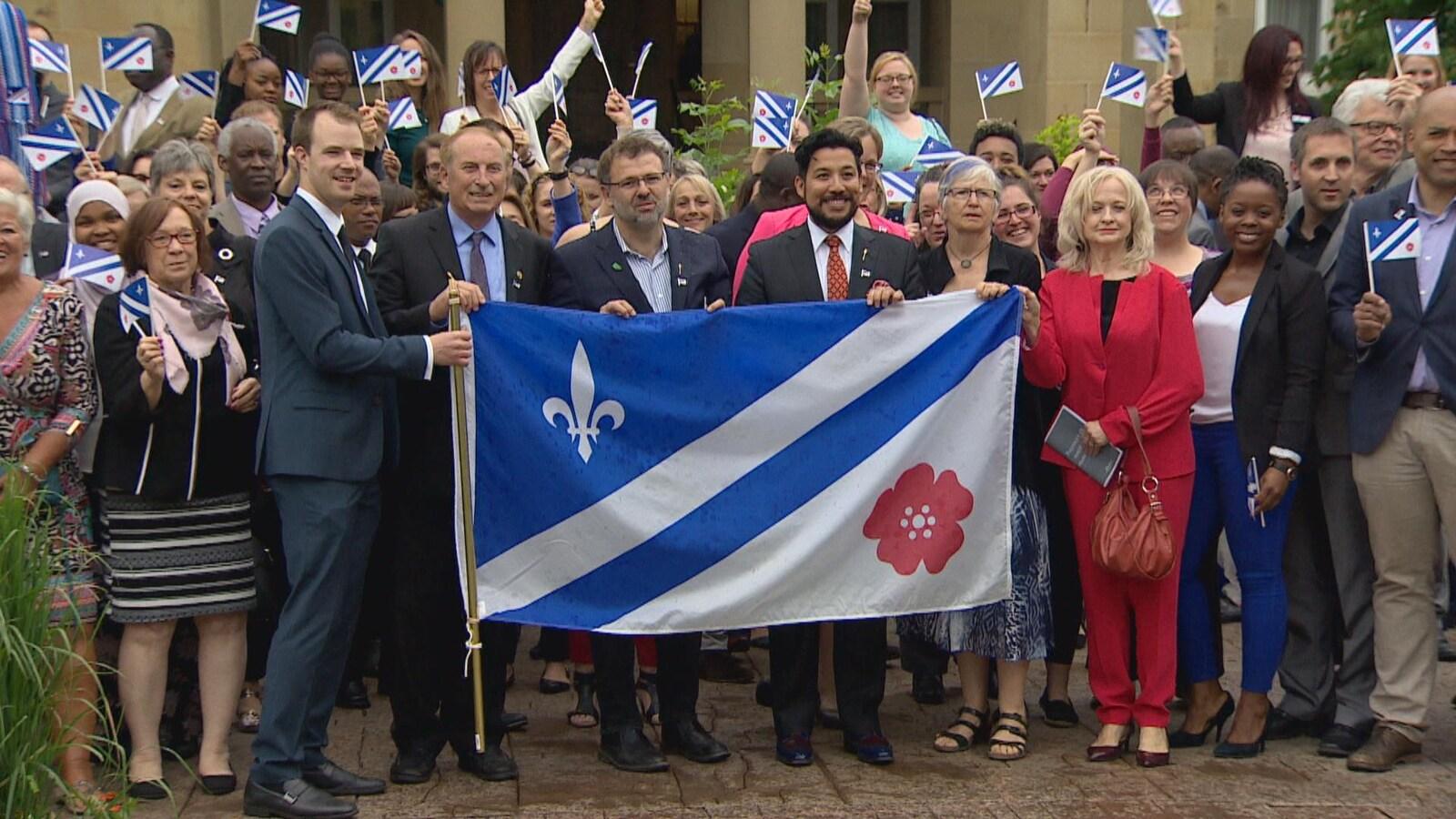 En avant-plan, le drapeau franco-albertain porté par quatre personnes, derrière eux une foule avec des petits drapeaux à la main. 14 juin 2017 : Jour de célébration pour la francophonie albertaine. Son drapeau devient un emblème provincial.