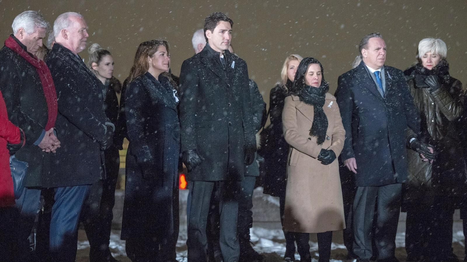 Les dignitaires sont debouts, dehors, sous la neige qui tombe.