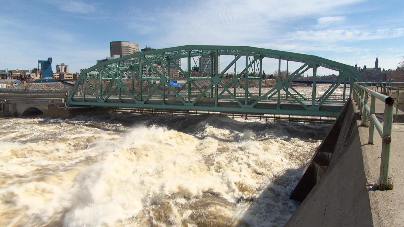 L'eau tumultueuse atteint presque le tablier du pont.