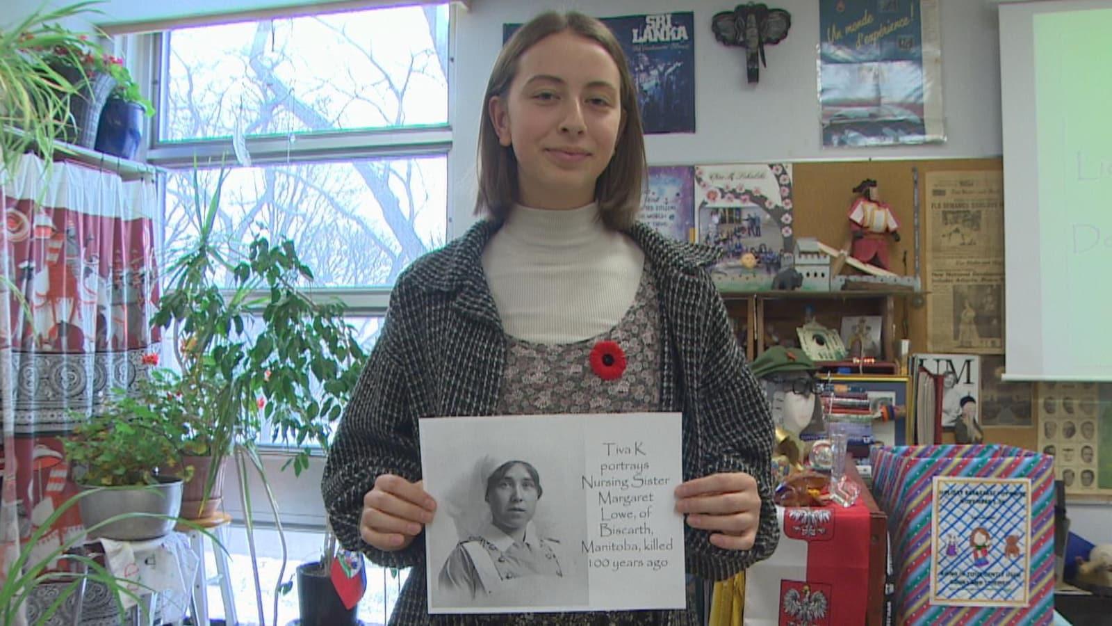 Dans une classe, une adolescente aux cheveux bruns mi-longs tient une feuille sur laquelle figure le dessin d'une infirmière de l'époque, annoté du texte suivant : Tiva K portrays Nursing Sister Margaret Lowe, of Biscarth, Manitoba, killed 100 years ago.