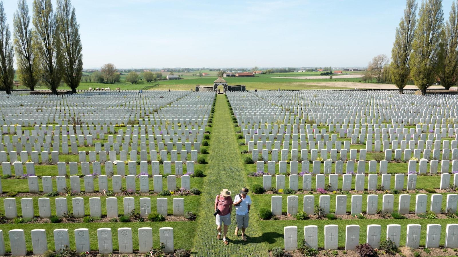 Un couple se promène dans l'allée centrale entre les tombes.