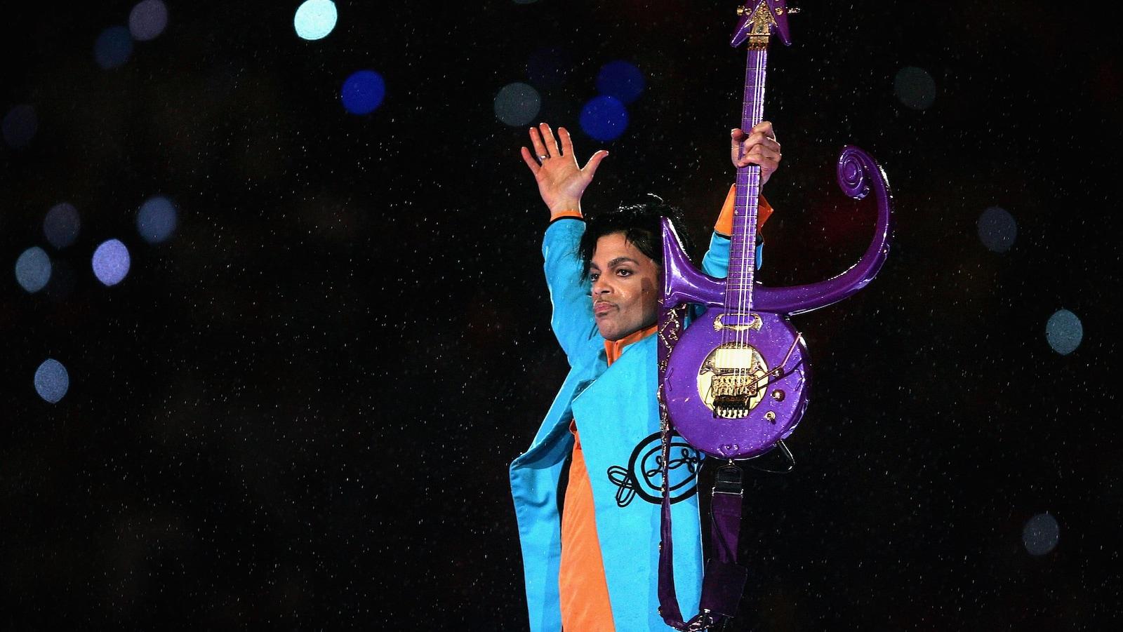 Prince en costume bleu brandit sa guitare