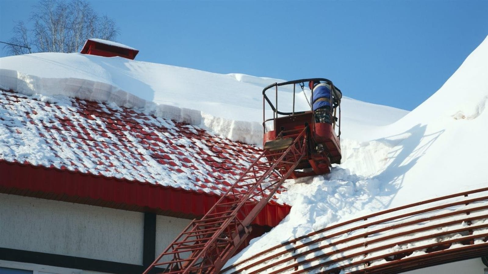 Un professionnel en train de déneiger un toit.