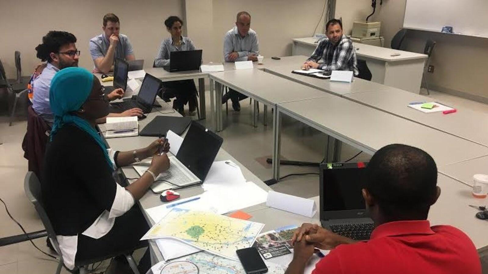 Des étudiants et des entrepreneurs sont assis sur des chaises, devant des tables de travail, à l'intérieur d'une salle de classe. Les étudiants prennent des notes à l'aide d'un ordinateur portable.