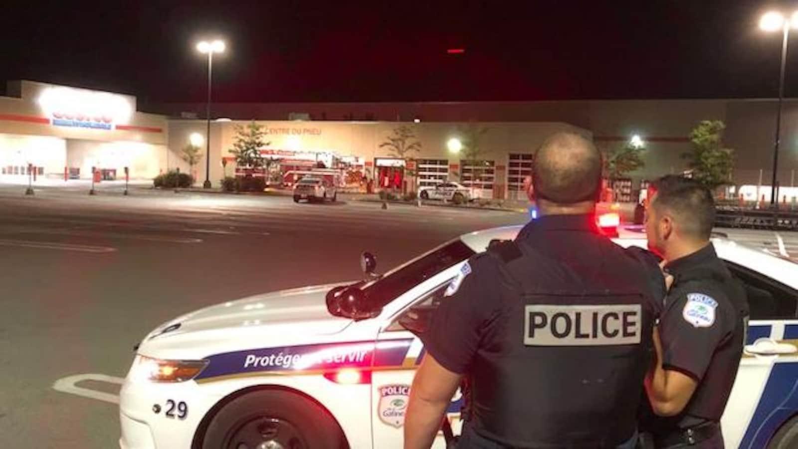Deux policiers devant un véhicule du Service de police de la Ville de Gatineau dans le stationnement des Promenades Gatineau.