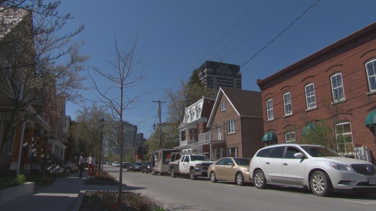 Les maisons à l'architecture distinctive sont aménagées le long d'une rue qui permet d'apercevoir au loin les édifices fédéraux de la promenade du Portage.