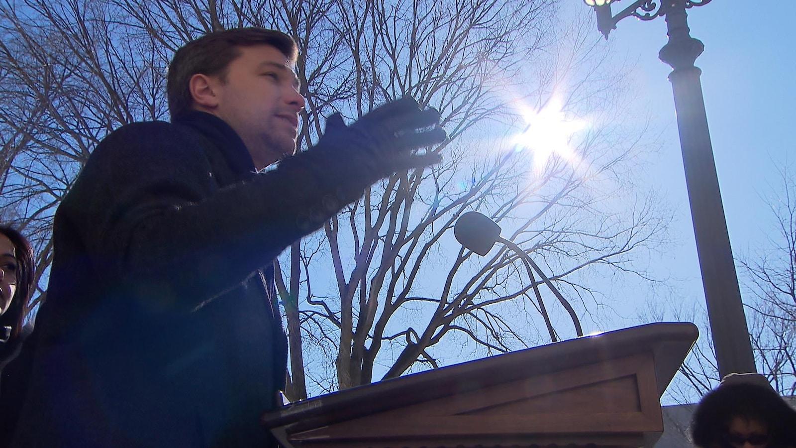 Gabriel Nadeau-Dubois parle derrière un podium placé à l'extérieur. On voit des arbres en arrière-plan.