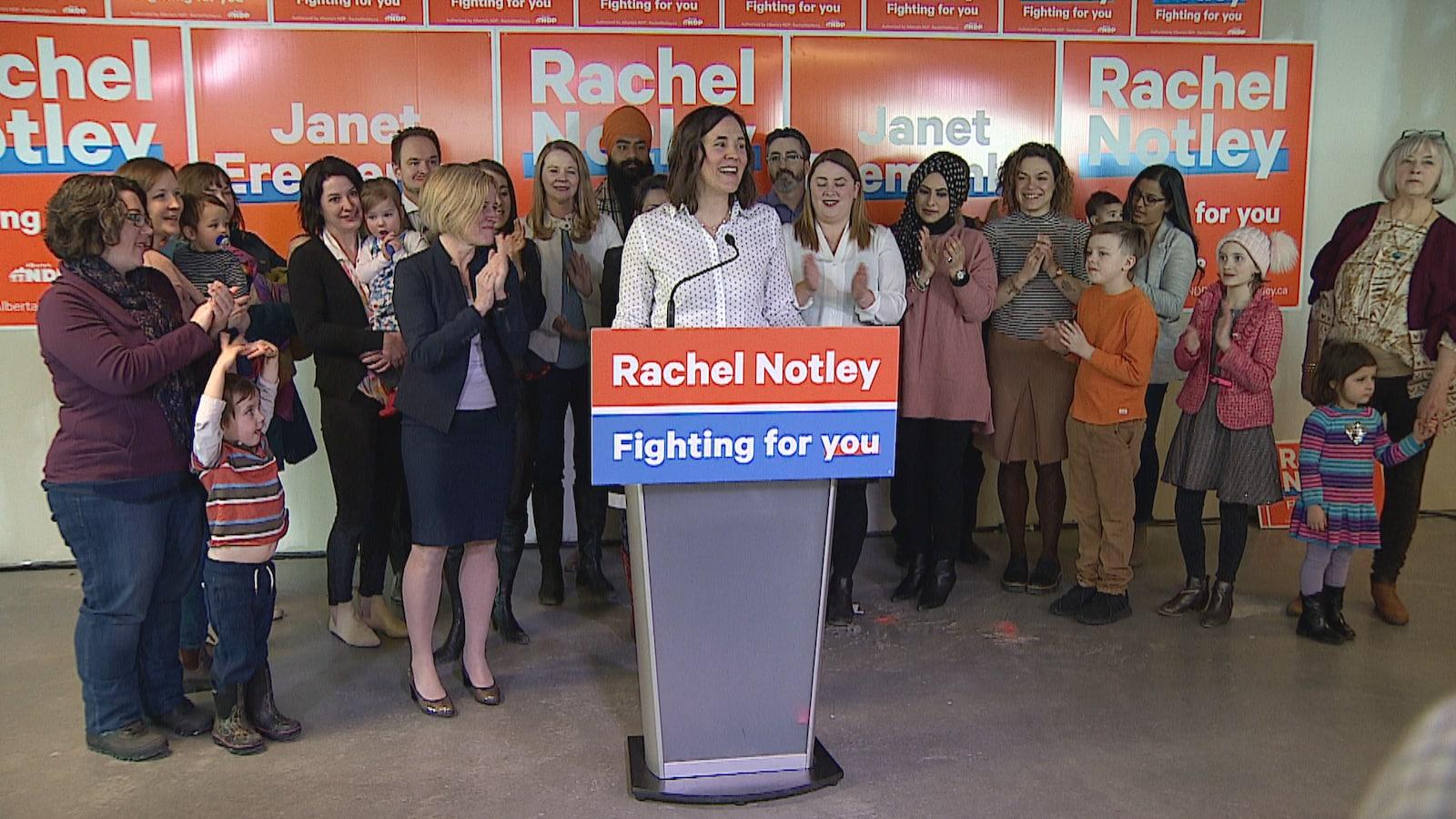 La candidate Janet Eremenko est entourée de Rachel Notley et d'une dizaine de femmes et d'enfants, devant des pancartes électorales.