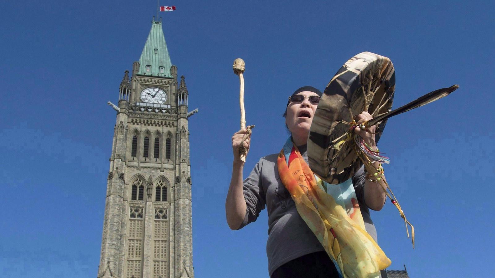 Une femme autochtone joue du tambourin devant l'édifice du Parlement à Ottawa.