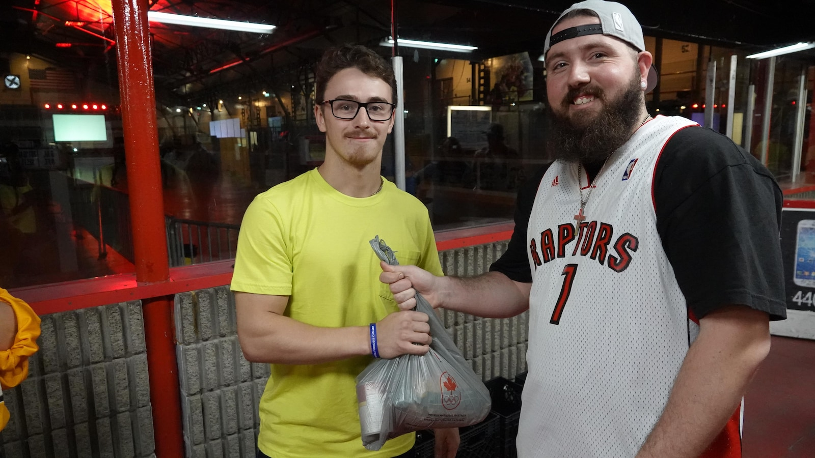 Un fan de basketball abordant son gilet des Raptors pose fièrement avec son don en denrée non périssable.