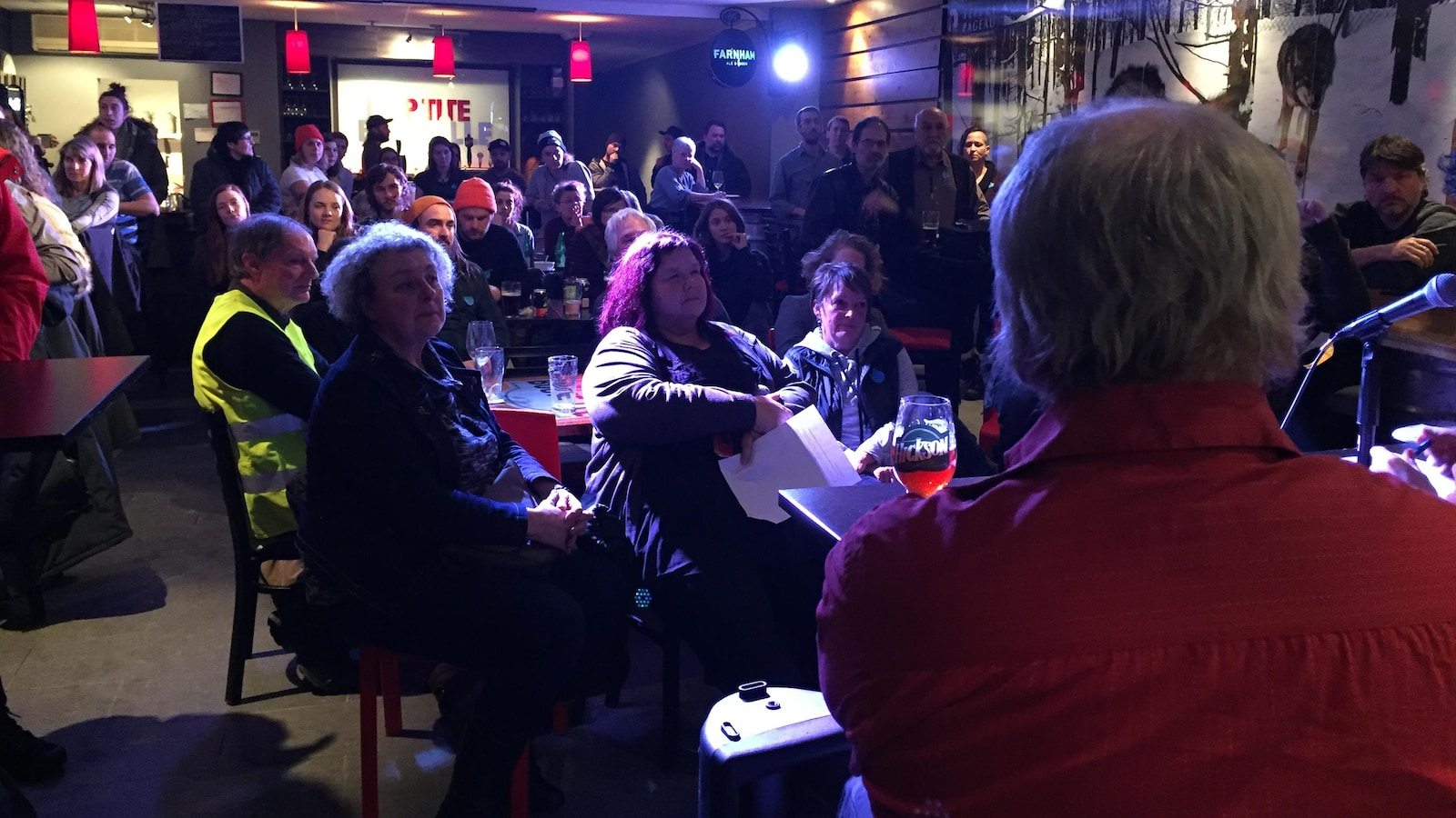 Un bar est rempli de gens qui écoutent parler des hommes assis devant la foule.