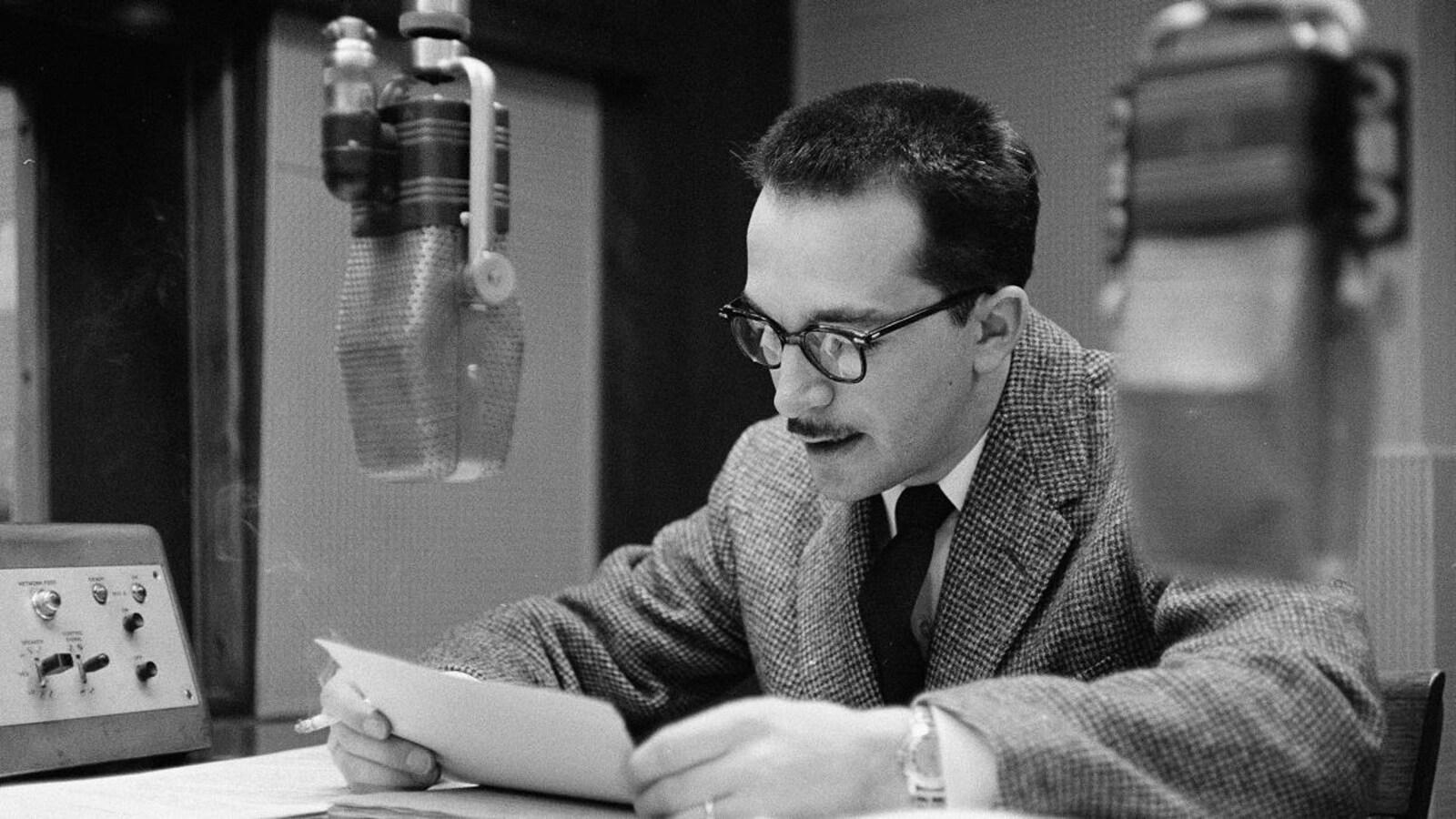 Raymond Charette lisant ses notes dans un studio de radio, derrière le micro.