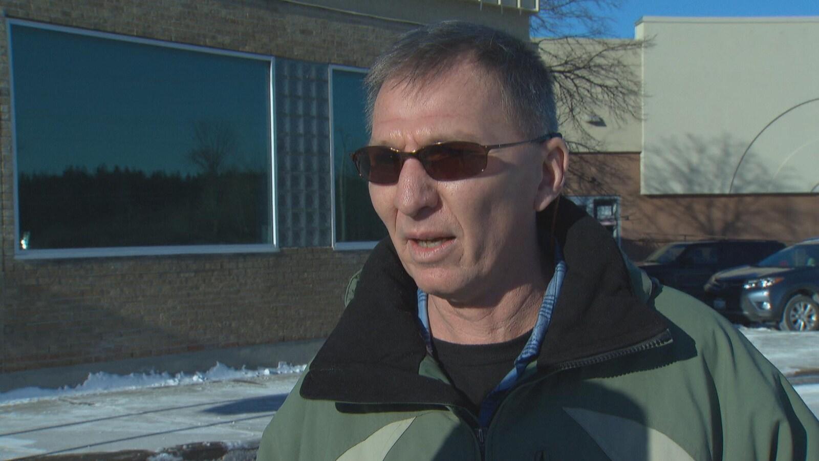 Réal Backaund répond aux questions d'une journaliste, dehors, devant un bâtiment, en hiver.
