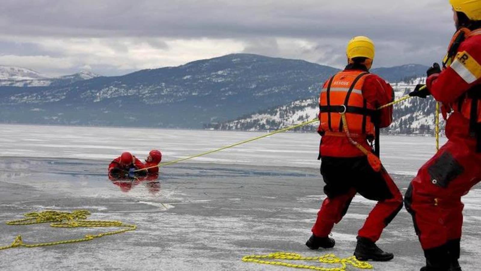 Des sauveteurs repêchent une personne d'un lac glacé.