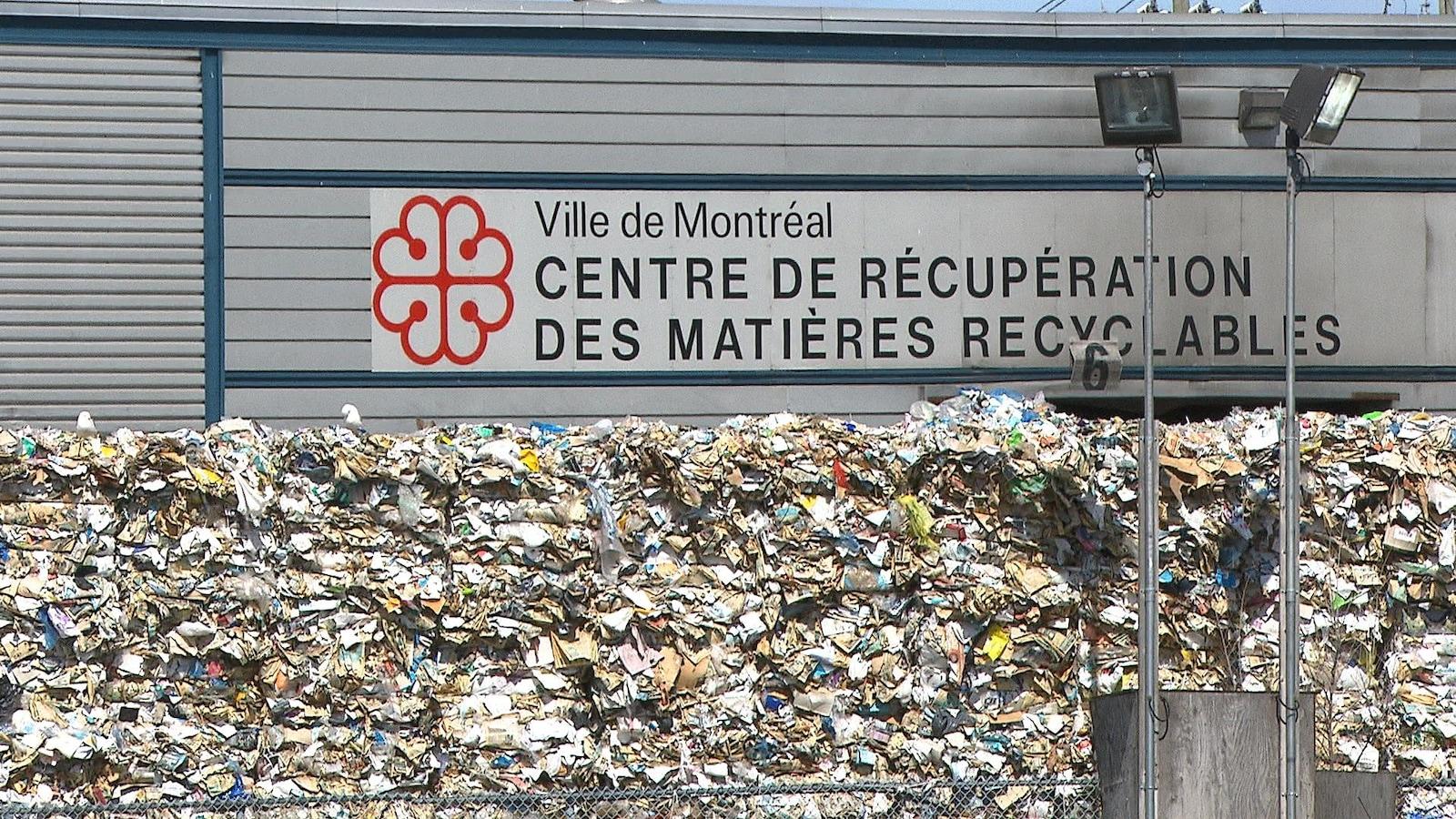 Une montagne de débris devant le mur du bâtiment sur lequel il est écrit: «Ville de Montréal, Centre de récupération des matières recyclables» avec le logo de la Ville de Montréal.
