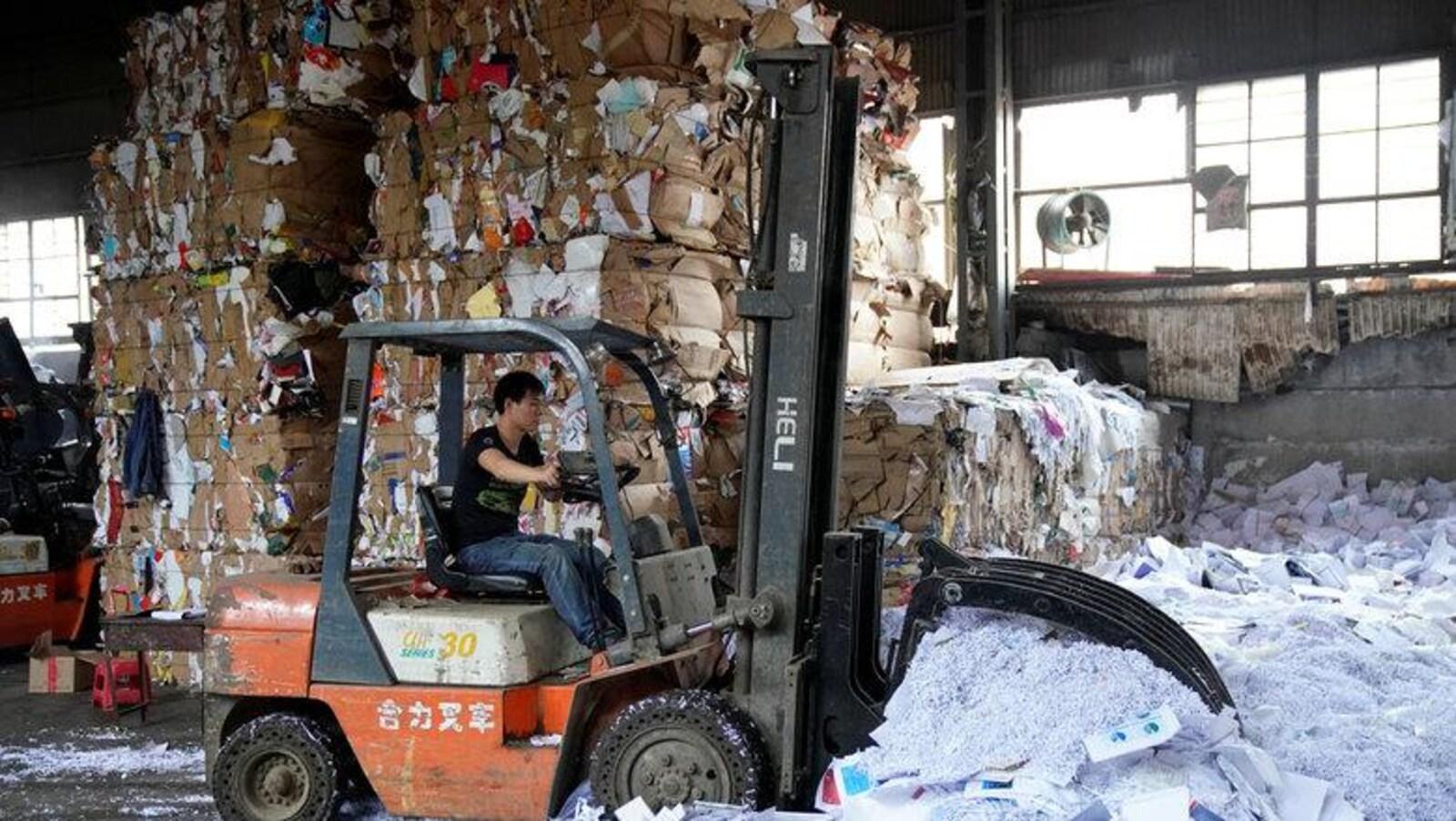 Un véhicule conduit par un ouvrier pousse une quantité importante de papier délaissé sur le sol d'une usine.