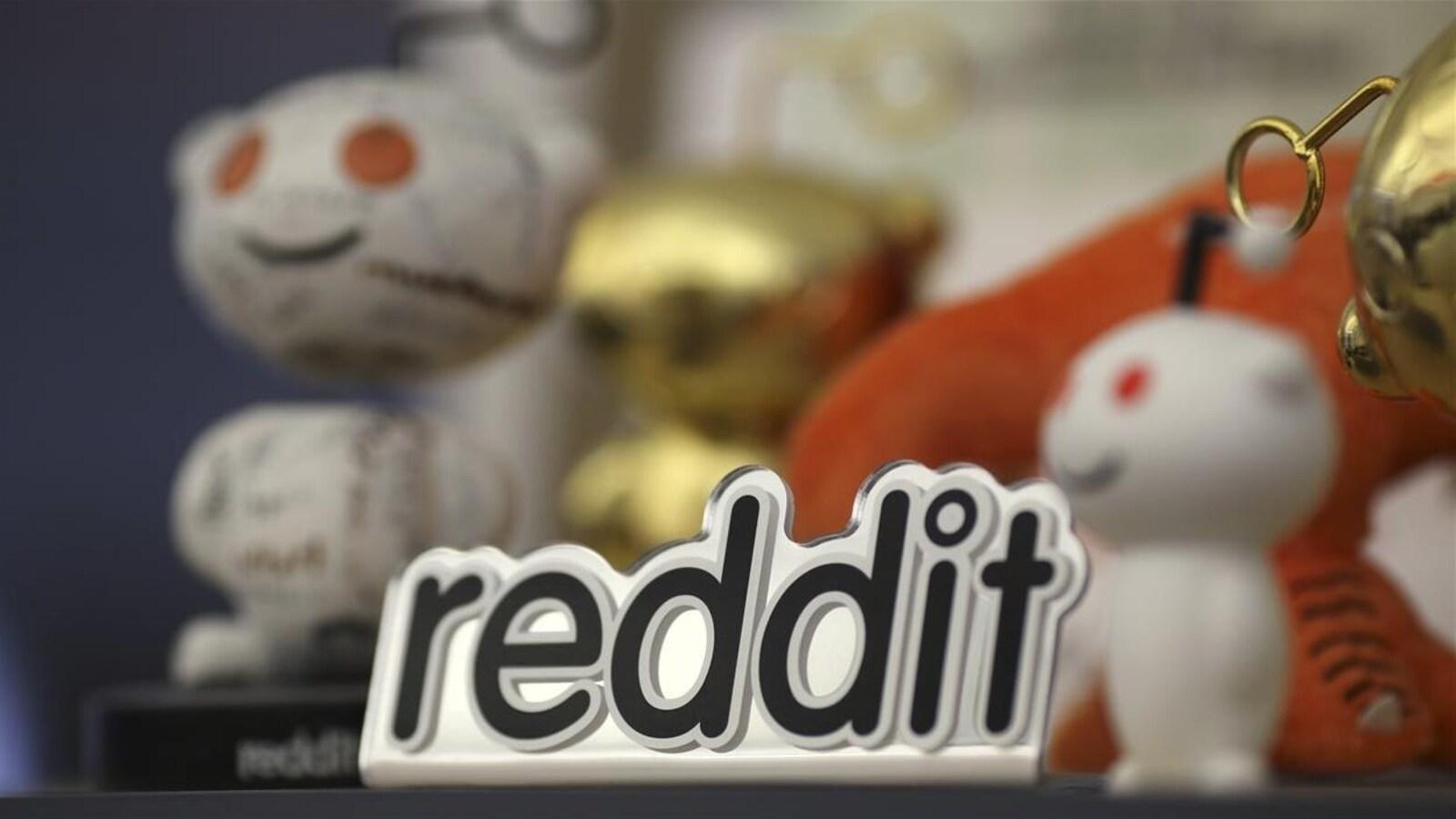 Le logo de Reddit est posé devant des petites figurines à l'image de l'entreprise