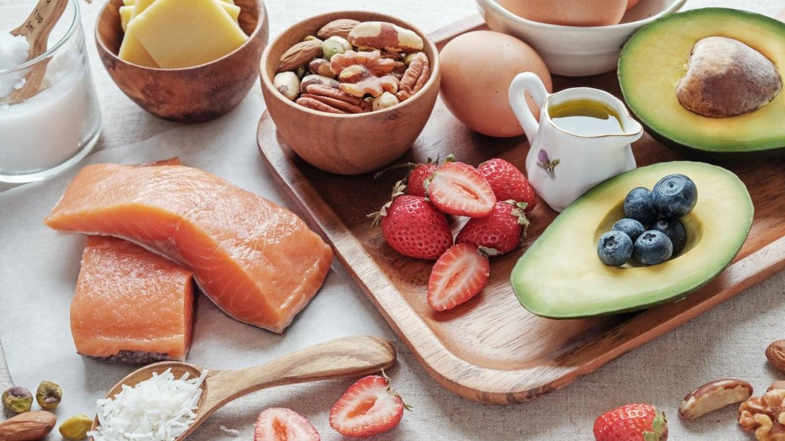 De l'avocat, des noix, des oeufs, du saumon et du fromage sont présentés sur un plateau en bois.