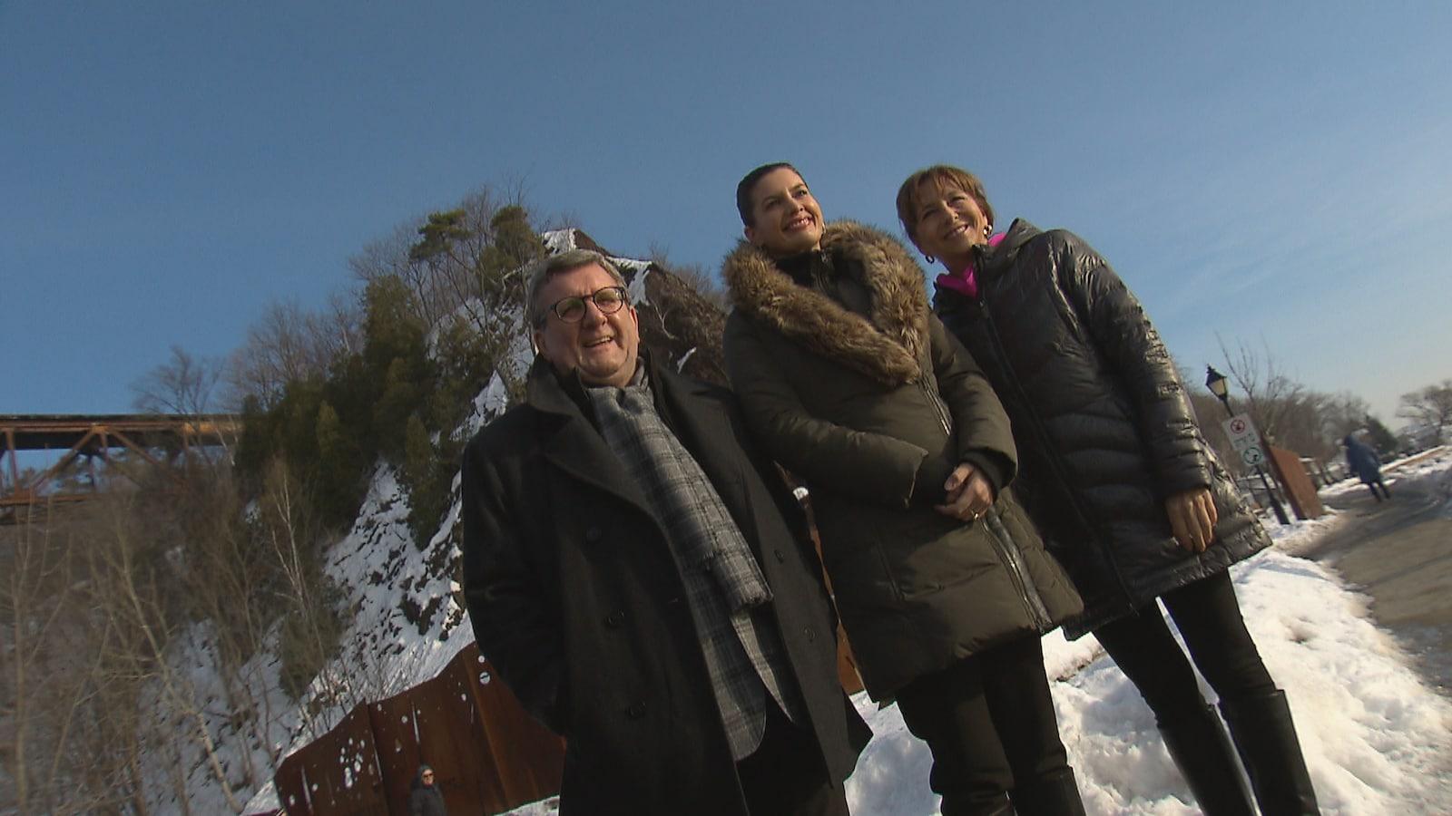 Photographie en contreplongée de Régis Labeaume, Geneviève Guilbault et Nathalie Roy prise en hiver. On aperçoit, à l'arrière-plan, le tracel et la falaise de Cap-Rouge.