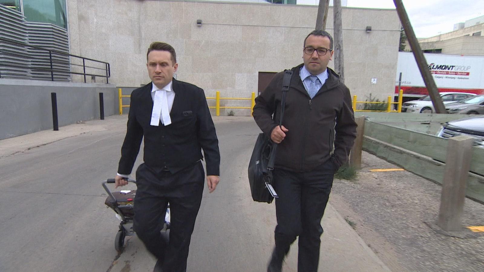 Deux hommes vêtus de noir marchent à l'extérieur.