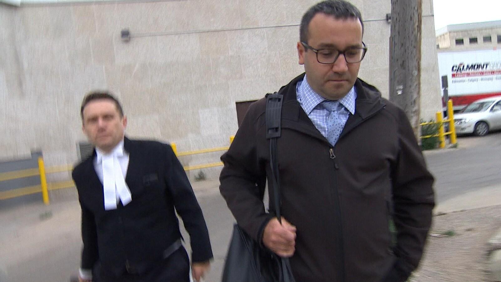 Rémi Dallaire marche, en regardant par terre, avec son avocat à sa gauche.