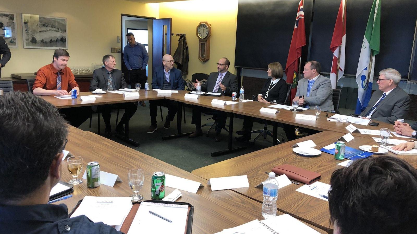 Un groupe de personnes assises autour d'une table dans une salle de réunion.