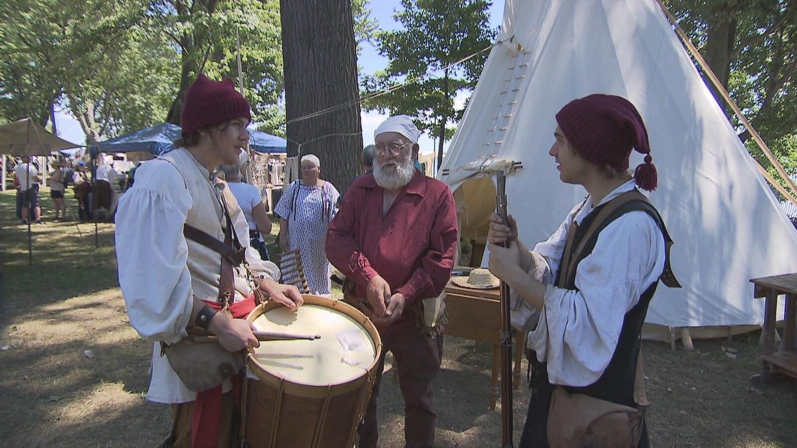 Trois hommes discutent alors qu'ils portent des vêtements de l'époque de la Nouvelle-France.