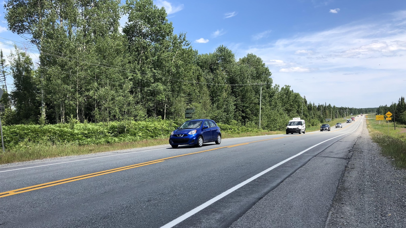 Des voitures circulent sur la route 117  qui traverse la réserve faunique La Vérendrye.
