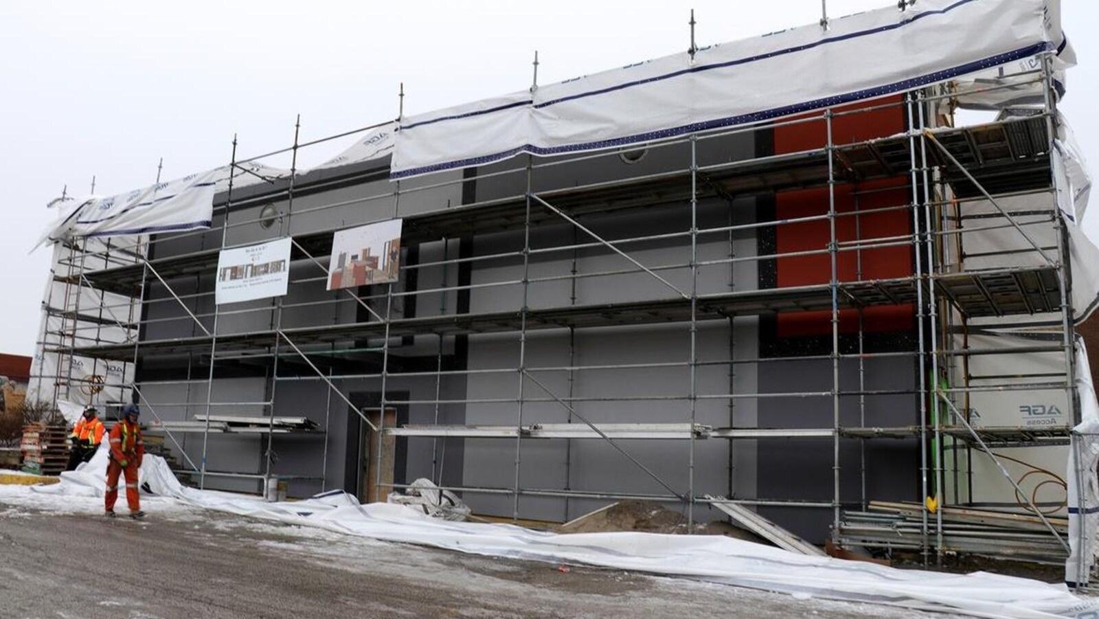 Des échafaudages se dressent sur toute la façade d'un bâtiment en rénovation. Des ouvriers sont au travail à gauche de l'image.