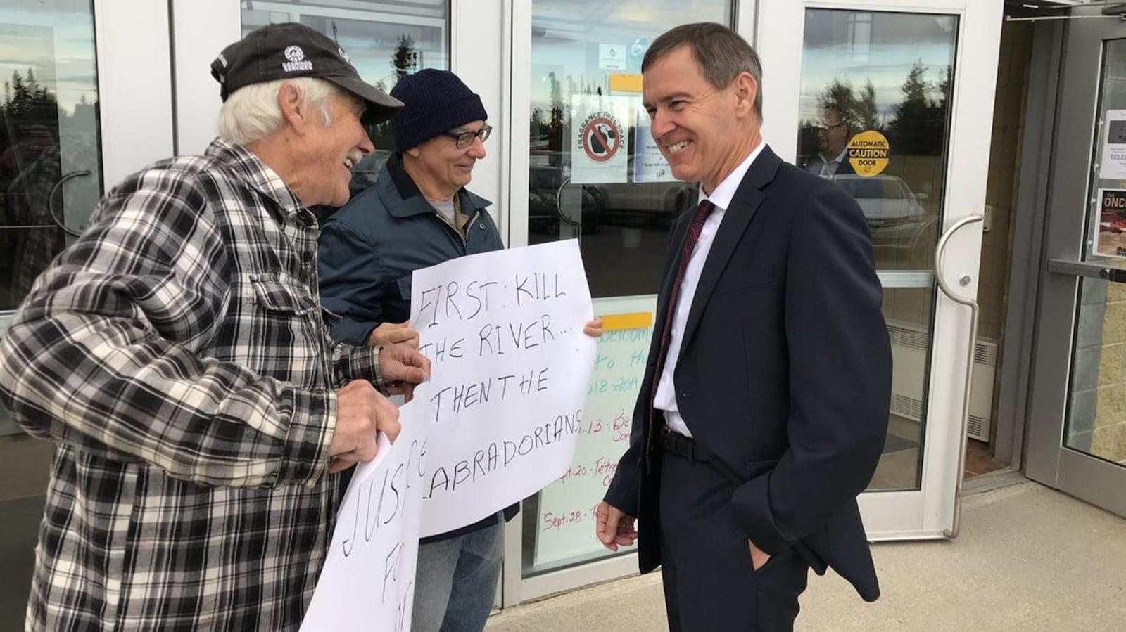 Le juge Richard LeBlanc converse avec deux manifestants devant le Centre Lawrence O'Brien, le 17 septembre 2018 à Happy Valley-Goose Bay, au Labrador.