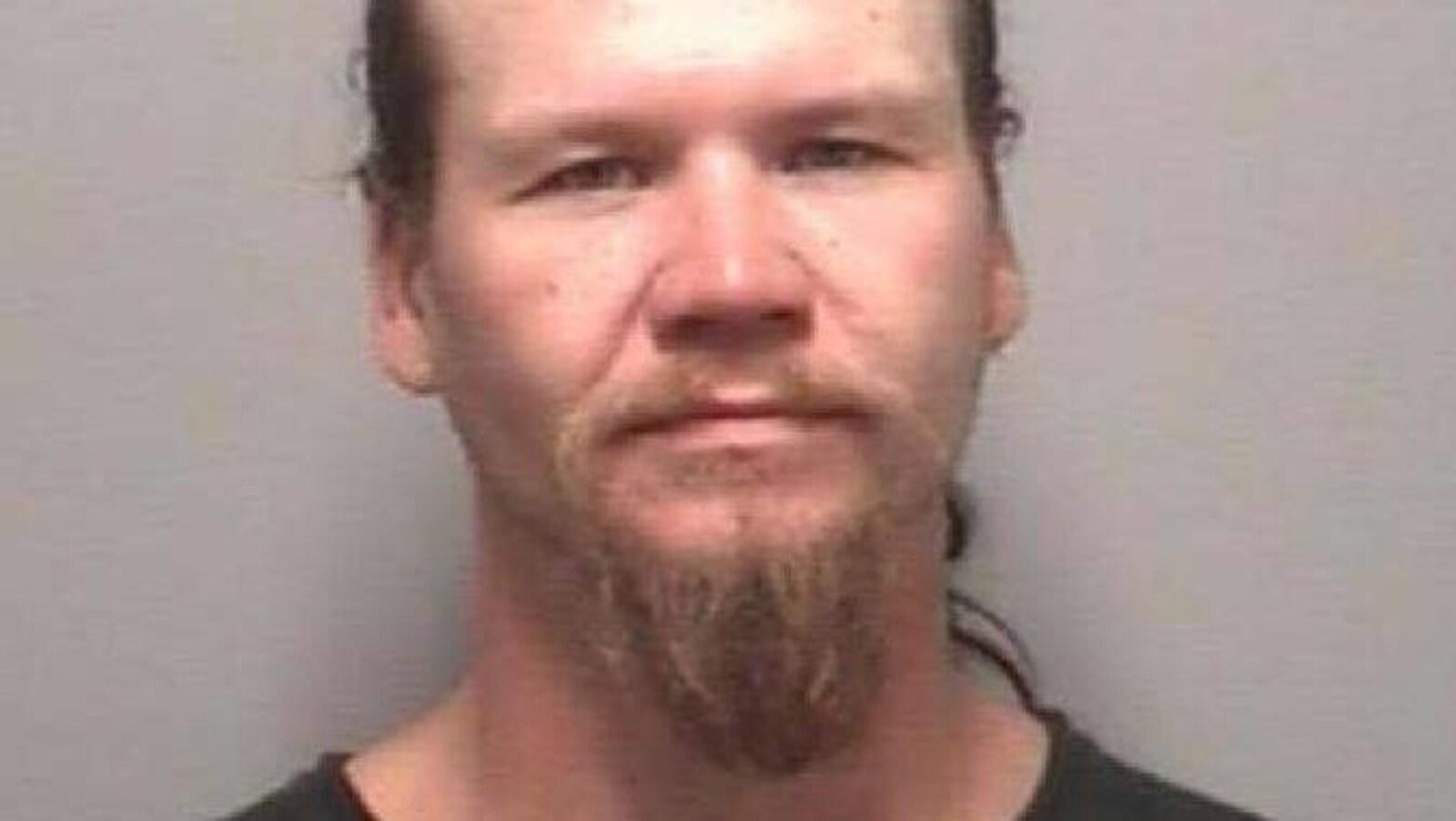 Photo d'un homme avec une barbichette à la mine patibulaire