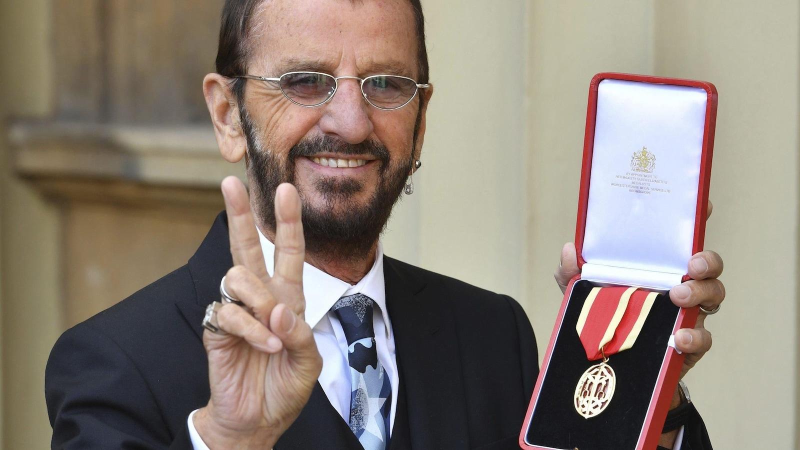 Ringo Starr tenant une médaille.