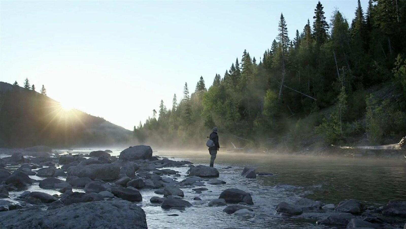 Personne debout sur une pierre au bord de la rivière Matapédia.