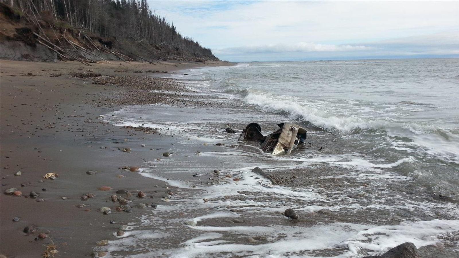 Des débris de ce qui ressemble à un reste de voiture sont enfouis dans le sable au travers des vagues du Saint-Laurent