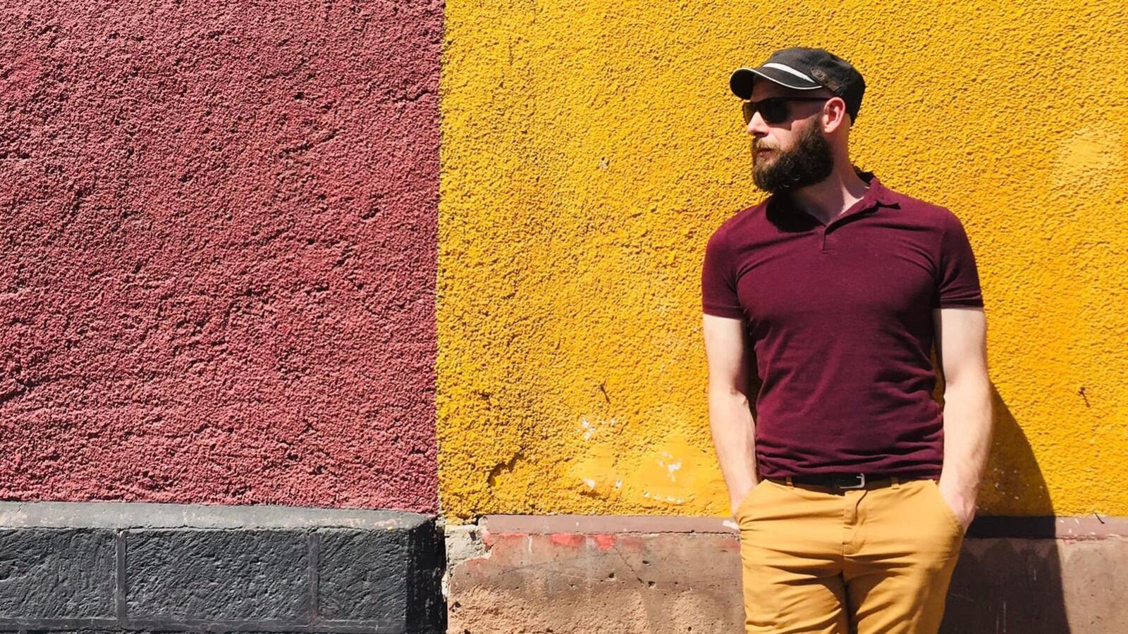 Un homme devant un mur jaune.
