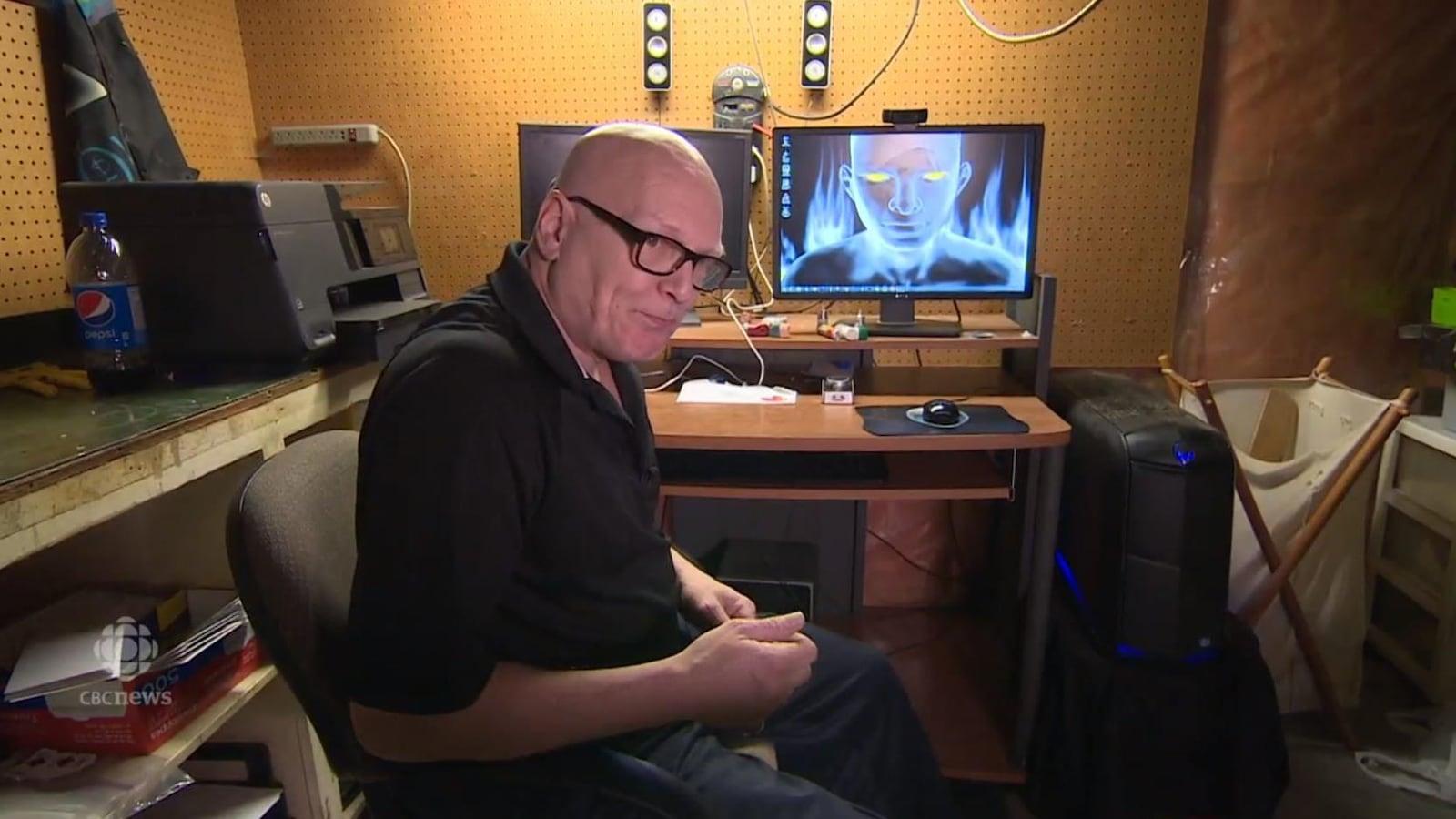 Un homme chauve est assis devant deux écrans d'ordinateur.