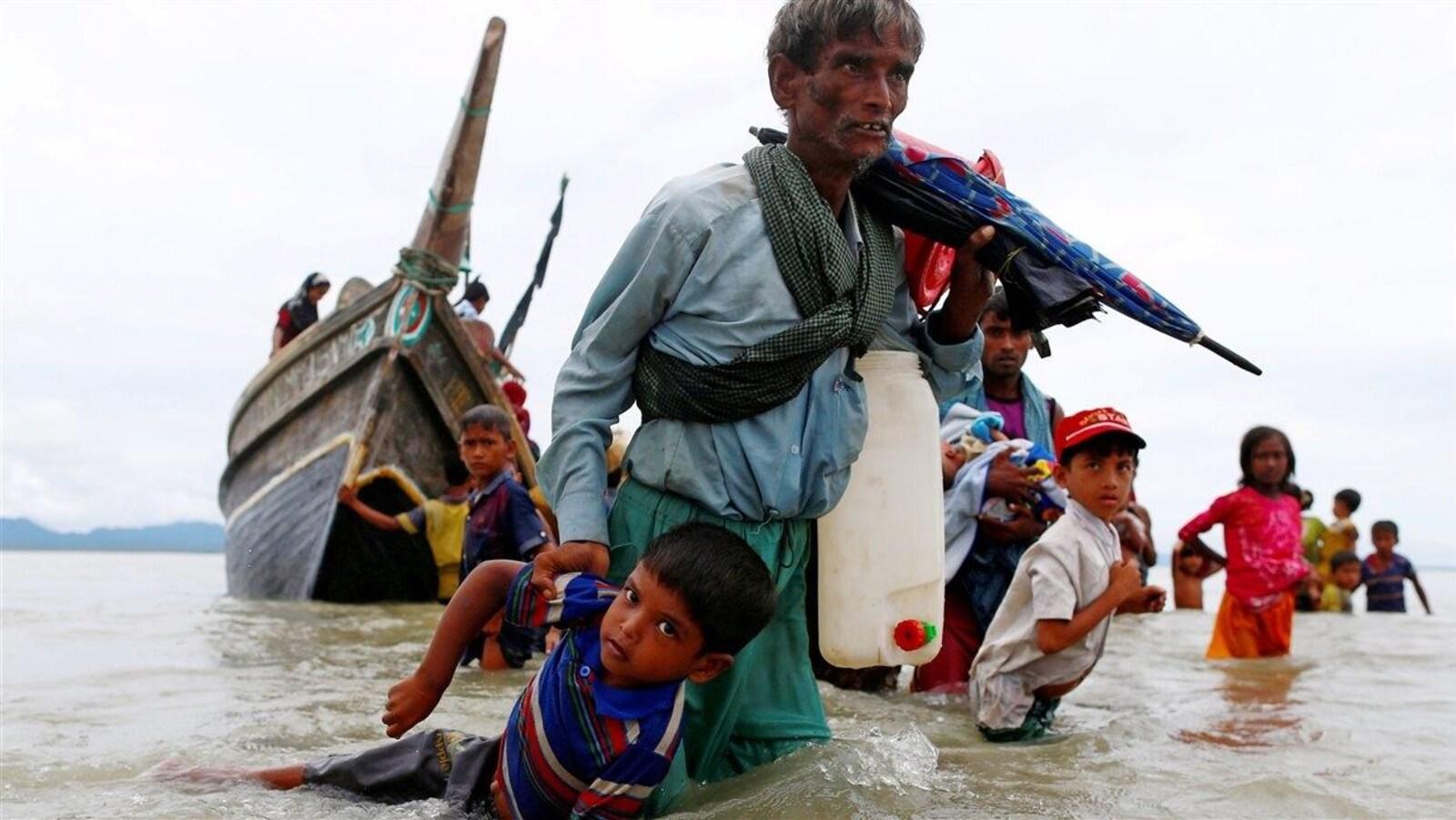 Un réfugié rohingya ayant de l'eau jusqu'aux genoux tire un jeune enfant par le bras.