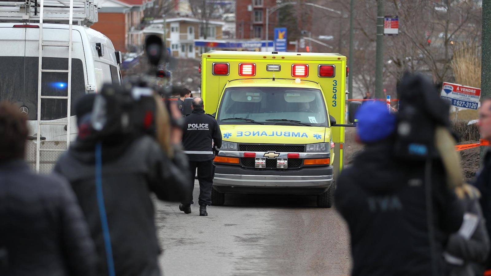 Une ambulance vient chercher le corps de Rosalie Gagnon. Des caméramans de différents réseaux filment la scène.